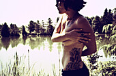Topless Young Woman With Tattoos Standing by Lake