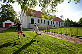 Children running over a meadow near a hotel, Fincken, Mecklenburg-Western Pomerania, Germany