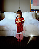 Girl with rag doll beside a hotel bed, Rotterdam, Netherlands