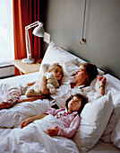 Mother and daughters in a hotel bed, Rotterdam, South Holland, Netherlands