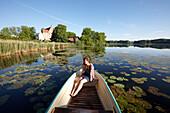 Young Woman in a rowing boat on lake Ulrichshusen, Ulrichshusen castle, Mecklenburg-West Pomerania, Germany