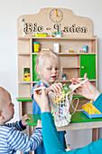 Little boy and girl playing shop together, bio shop with organic food, Bad Oeynhausen, North Rhine-Westphalia, Germany