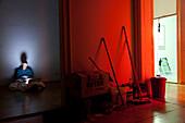 Frau sitzt auf Boden in einer leeren Wohnung, arbeitet am Laptop, Notebook, Computer, Parkett, Umzug, rotes Licht, Besen, Melancholie, MR, Leipzig, Sachsen, Deutschland