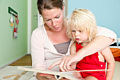 Mother and daughter reading a book in the nursery, two year old girl, MR, Bad Oeynhausen, North Rhine-Westphalia, Germany