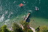 Young people bathing in lake Starnberg with pier, rowing boats and inflatable mattress, aerial view, Bavaria, Germany