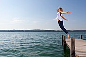 Girl jumps from a wooden pier into Lake Starnberg, Bavaria, Germany