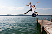 young couple jumps from pier into Lake Starnberg, Bavaria, Germany