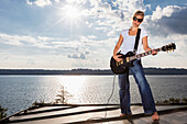 Young woman playing the guitar above Lake Starnberg, Upper Bavaria, Germany