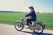 Old woman riding a moped, Upper Bavaria, Germany