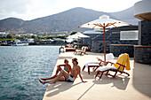 Paar sonnenbadend auf den Terrassen der Yachting Club Villas, Elounda Beach Resort, Elounda, Kreta, Griechenland