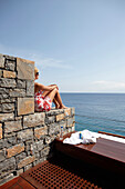 Woman sitting on stone step, looking towards the sea,  Beach Resort, Elounda, Crete, Greece