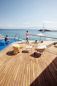Man and woman in the pool and on the deck of the Yachting Club Villas, Elounda Beach Resort, Elounda, Crete, Greece
