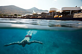 Diver underwater in front of Yachting Club, Elounda, Crete, Greece