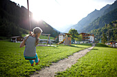 Girl playing on the zip line, outdoor area of Hotel Feuerstein, Pflersch, Gossensass, South Tyrol, Italy