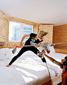 Woman playing air guitar with a mop brush on a bed sleeping eight people, Hotelroom, Zeeburg, Amsterdam, Netherlands