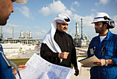 Men having a meeting, refinery in background, Ras Laffan Industrial City, Qatar
