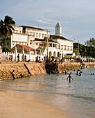 Kids bathing on Malindi beach, Mzingani Road, the shore of the Stone Town, tower of House of Wonders, Zanzibar Town, Zanzibar, Tanzania, East Africa