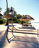 Sunshades and traditional beds made out of coconut ropes for guests, beach of Blue Oyster Hotel, Jambiani, south east Zanzibar, Tanzania, East Africa