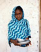 Girl with blue Kanga cloth in front of coral stone house, Jambiani village, Zanzibar, Tanzania, East Africa