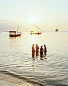 Boys bathing at Forodhani beach, cargo dhows on the western tip of Stone Town, Zanzibar, Tanzania, East Africa