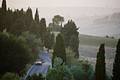 Vintage car on a country road at the Montalcino region at dusk, Tuscany, Italy, Europe