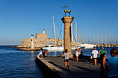 Columns at the entrance of Mandraki harbour and the Agios Nikolaos Fortress in the sunlight, Rhodes town, Rhodes, Dodecanese Islands, Greece, Europe