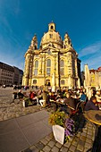 People at sidewalk cafes in the Neumarkt area with the Frauenkiche church in background, Dresden, Saxony, Germany