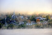 Early morning mist and autumn coloured in Grande Piles Village and St Maurice river  Quebec, Canada