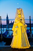 A masked woman in front of gondolas at dawn at the carnival in Venice, Italy, Europe