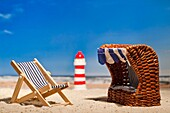 Still life of a miniature lighthouse, deck chair and roofed wicker beach chair