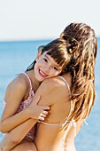 Daughter giving a hug to her mother and looking at camera in the seashore