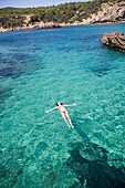 Woman floating in water at a beach in Portinatx, Ibiza, Balearic Islands, Spain