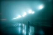 Figure walking on a wet foggy night