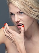 Portrait of a young woman with bright orange nail polish