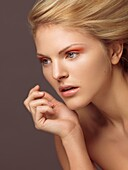 Beauty portrait of a young woman with bright orange eye shadows