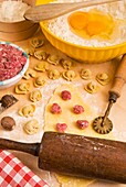 Homemade Tortellini, ring-shaped pasta  They are typically stuffed with a mix of meat pork loin, prosciutto and cheese, Italian gastronomy, Italy