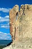 Sandstone cliff balances precariously at El Morro National Monument, New Mexico, USA