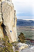 Rock climbing a route called Sancho Rama which is rated 5, 10 and located on the Upper Comp Wall at Castle Rocks State Park near the town of Almo in southern Idaho