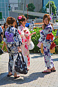Three young Japanese women in yukata summer kimono stroll in the Roppongi District of central Tokyo, Japan.