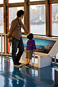 A Japanese father and his son visit the Museum of Maritime Science for a view of Tokyo Bay on a clear sunny day in the Odaiba District of in Tokyo, Japan.