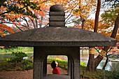 Seen through a stone lantern, a woman pauses to admire Japanese maple trees in bright autumn colors at Koishikawa Korakuen Gardens, an Edo Period Japanese garden located in the Bunkyo-ku district of Tokyo, Japan.