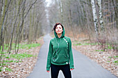 Woman doing sport in park listening to music