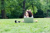 Businesswoman with laptop relaxing in park at lunch-time