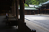 A visitor prays at the Outer Shrine of Meiji-Jingu Shrine, located in the Shibuya district of Tokyo, Japan.