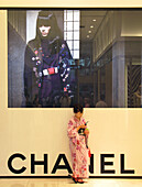 A young Japanese woman wearing a yukata traditional summer kimono uses her cellphone while casually leaning against a huge wall-size Chanel advertisement at Takashimaya Times Square department store in the Shinjuku district of Tokyo, Japan.