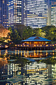 The Shiodome business complex forms a solid wall behind Hama-Rikyu Gardens with its refined Nakajima Teahouse at twilight, and functions as a contemporary Borrowed Landscape (a tradition in Japanese garden design incorporating distant scenery), with spark