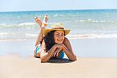Portrait of a brunette woman in bikini lying down on the beach