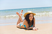 Portrait of a brunette woman in bikini lying down on the beach, smiling at camera