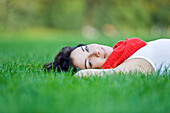 Beautiful woman lying down in park looking at camera