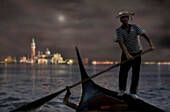 Gondolier wtih gondola at night with a city view in the background, Venice, Italien